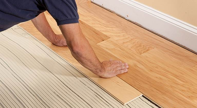 Person installing wood flooring using TEC adhesive.