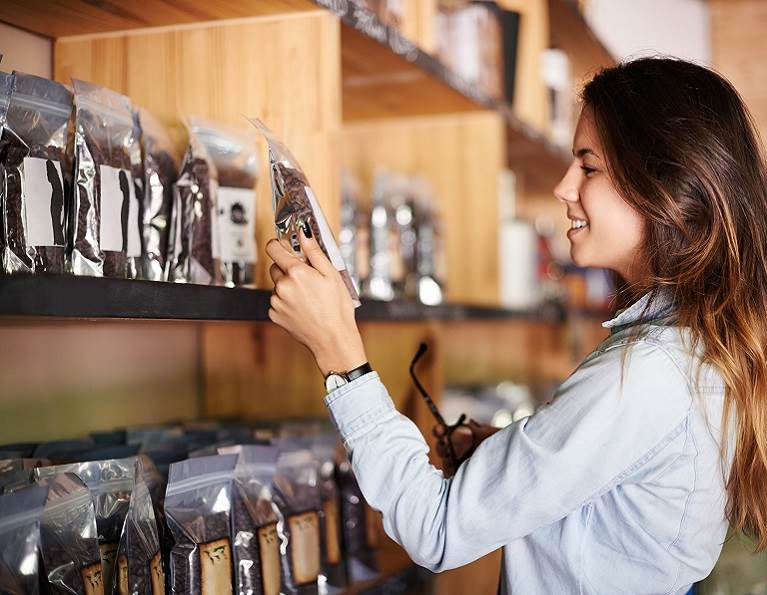 Woman shopping a shelf of coffee packaged with flexible packaging using adhesives from H.B. Fuller.
