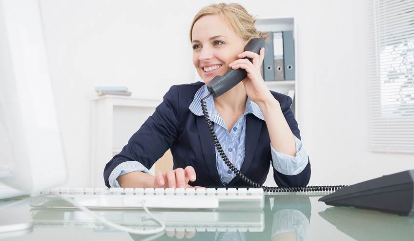 Woman in an office setting on a phone landline.